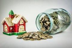 Alloggi e un barattolo di vetro con le monete su un fondo bianco Fotografia Stock Libera da Diritti