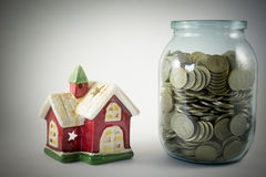 Alloggi e un barattolo di vetro con le monete su un fondo bianco Fotografie Stock
