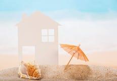 Alloggi fatta di carta, le coperture, stella in sabbia contro il mare Immagine Stock Libera da Diritti