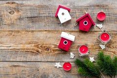 Alloggi i giocattoli e le candele per la celebrazione del nuovo anno con i rami di albero della pelliccia sul modello di legno de Immagine Stock Libera da Diritti