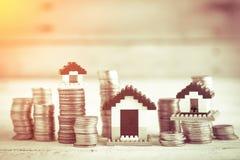 Alloggi i modelli con le monete impilate al patrimonio aziendale di legno c della tavola Immagini Stock