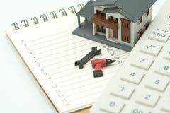 Alloggi i modelli ed i modelli dell'attrezzatura disposti su una riparazione e su una costruzione della casa della lista di posti Fotografia Stock Libera da Diritti