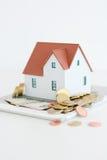 """Alloggi il †di concetto di proprietà """"una casa di modello su un mucchio delle monete Immagine Stock"""