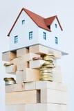 """Alloggi il †di concetto di proprietà """"una casa di modello su un mucchio delle monete Fotografia Stock Libera da Diritti"""