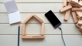 Alloggi il blocchetto e lo Smart Phone di legno di simbolo con il taccuino e la penna Fotografia Stock Libera da Diritti