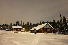 Alloggi il chalet durante precipitazioni nevose nella foresta dell'inverno degli alberi a nig Fotografie Stock Libere da Diritti