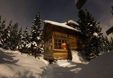 Alloggi il chalet durante precipitazioni nevose nella foresta dell'inverno degli alberi a nig Fotografie Stock