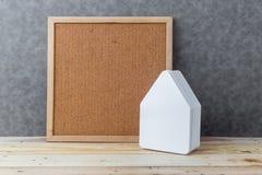 Alloggi il concetto con il cartone di forma della casa sul pavimento e sul gre di legno Immagini Stock