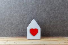 Alloggi il concetto con il cartone di forma della casa sul pavimento e sul gre di legno Fotografie Stock