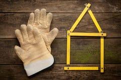 Alloggi il concetto con il metro giallo ed i guanti di lavoro Fotografia Stock