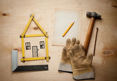 Alloggi il concetto con il metro giallo ed i guanti di lavoro Fotografia Stock Libera da Diritti
