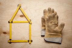Alloggi il concetto con il metro giallo ed i guanti di lavoro Immagini Stock