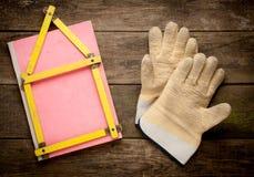 Alloggi il concetto con il metro giallo ed i guanti di lavoro Immagine Stock Libera da Diritti