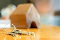 Alloggi il concetto, la chiave ed il modello della casa messo sulla tavola Immagine Stock Libera da Diritti
