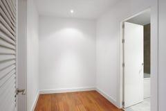 Alloggi il corridoio con le pareti bianche ed il pavimento di legno Fotografia Stock Libera da Diritti