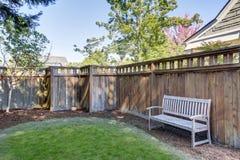 Alloggi il cortile posteriore con il banco di legno che fa una pausa il recinto Immagini Stock