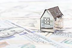 Alloggi il denaro contante di modello ed americano del dollaro sulla tavola della scrivania Immagine Stock