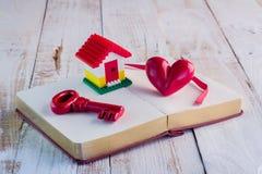 Alloggi il modello con cuore e la chiave rossa sul taccuino jpg Immagine Stock