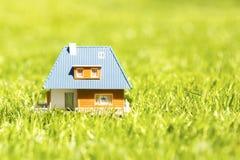 Alloggi il modello di scala su erba verde con lo spazio della copia Fotografia Stock