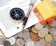 Alloggi il modello e la bussola con la penna di palla sul fondo delle monete Immagini Stock Libere da Diritti
