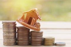alloggi il modello sulle monete dei soldi, i piani per l'abitazione, sedere verdi di risparmio Fotografia Stock Libera da Diritti