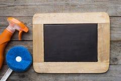 Alloggi il prodotto e la lavagna di pulizia sulla tavola di legno Fotografie Stock