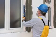 Alloggi il rinnovamento, l'isolamento della parete del polistirolo, strumento livellato Fotografia Stock