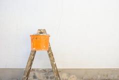 Alloggi il rinnovamento, la scala ed il secchio davanti ad una parete vuota della casa Fotografia Stock Libera da Diritti