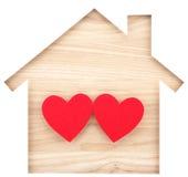 Alloggi il ritaglio di carta a forma di e due cuori su legname di legno naturale Fotografia Stock