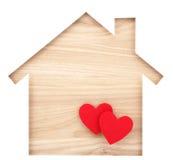 Alloggi il ritaglio di carta a forma di e due piccoli cuori su legno naturale l Fotografie Stock Libere da Diritti