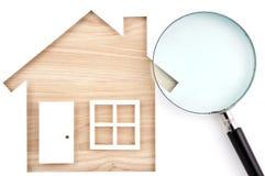 Alloggi il ritaglio e la lente di carta a forma di su legname di legno naturale Fotografia Stock