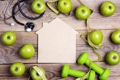 Alloggi il simbolo con le teste di legno e le mele verdi con nastro adesivo di misurazione Immagine Stock