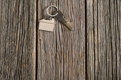 Alloggi il simbolo di chiavi sul vecchio fondo di legno del pavimento Fotografie Stock