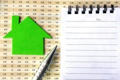 Alloggi il simbolo, il blocchetto per appunti e la penna sul rapporto finanziario Fotografia Stock