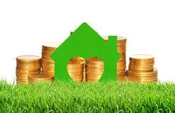 Alloggi il simbolo sopra le monete dorate in erba verde su bianco Fotografie Stock