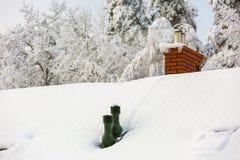 Alloggi il tetto con il camino al giorno di inverno nevoso Immagine Stock Libera da Diritti