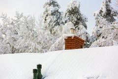 Alloggi il tetto con il camino al giorno di inverno nevoso Fotografia Stock Libera da Diritti