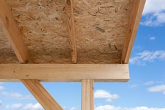 Alloggi il tetto con la gronda, i fasci di legno ed il cartone di fibra Fotografia Stock