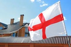 Alloggi il tetto e la bandiera d'ondeggiamento del ` s dell'Inghilterra Immagine Stock