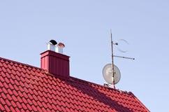 Alloggi il tetto rosso con il camino ed il disco della TV Fotografia Stock