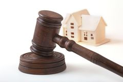 Alloggi l'asta, il martello dell'asta, il simbolo dell'autorità e la casa miniatura Concetto dell'aula di tribunale Fotografie Stock