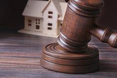 Alloggi l'asta, il martello dell'asta, il simbolo dell'autorità e la casa miniatura Concetto dell'aula di tribunale Fotografia Stock