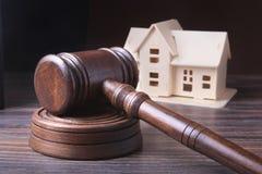 Alloggi l'asta, il martello dell'asta, il simbolo dell'autorità e la casa miniatura Concetto dell'aula di tribunale Immagini Stock