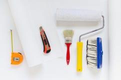 Alloggi l'attrezzatura della riparazione, rotolo bianco della carta da parati con il rullo di pittura, la spazzola, la misura di  Fotografia Stock