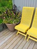 Alloggi l'esterno decorato con le sedie ed i fiori gialli Fotografie Stock Libere da Diritti