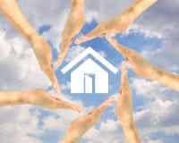 Alloggi l'icona nelle mani della gente su un fondo delle nuvole Immagine Stock