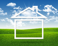 Alloggi l'icona su fondo di erba verde e del blu Fotografia Stock