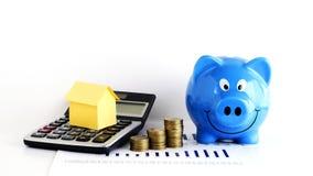 Alloggi la carta sul calcolatore e monete e porcellino salvadanaio per il prestito immobiliare Fotografia Stock