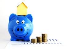 Alloggi la carta sul porcellino salvadanaio e le monete per il concetto di prestiti Fotografia Stock Libera da Diritti