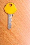 Alloggi la chiave con i cappucci gialli dei cappotti della plastica sulla tavola Immagine Stock